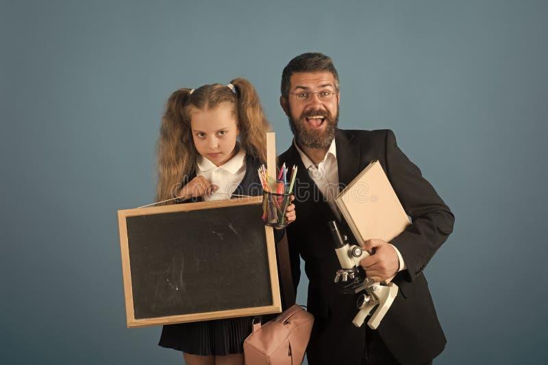 Pai e estudante com as caras felizes e mal-humoradas no azul fotos de stock