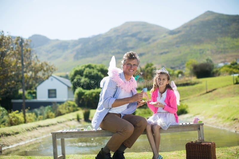 Pai e filha de sorriso no traje feericamente que come um chá fotos de stock royalty free