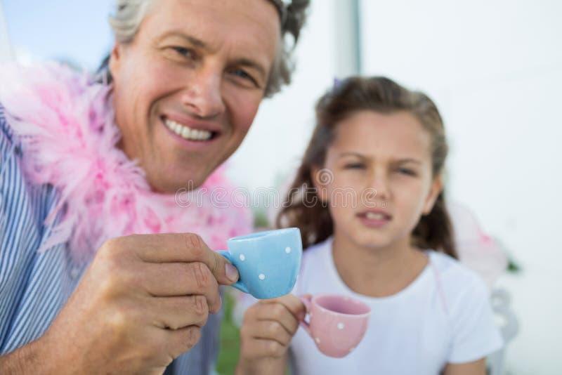 Pai e filha de sorriso no traje feericamente que tem um tea party imagem de stock