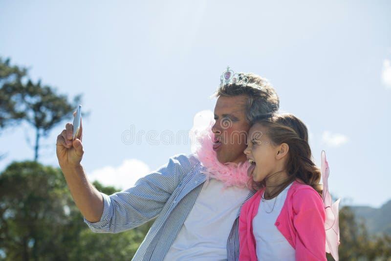 Pai e filha de sorriso no traje feericamente que toma o selfie no telefone celular foto de stock