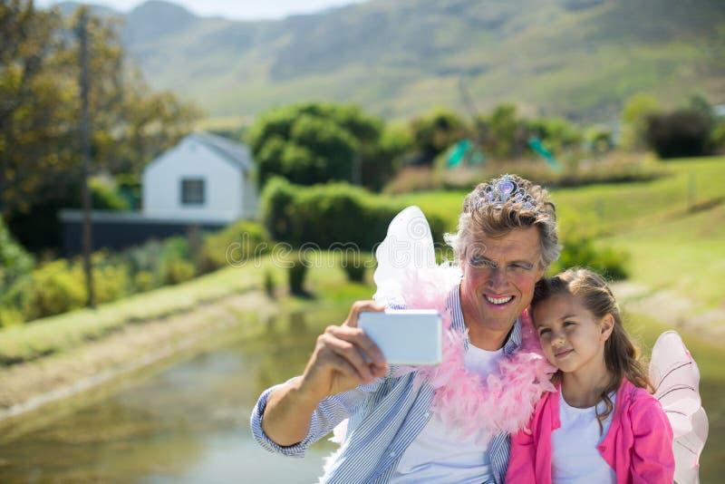 Pai e filha de sorriso no traje feericamente que toma o selfie no telefone celular fotografia de stock royalty free