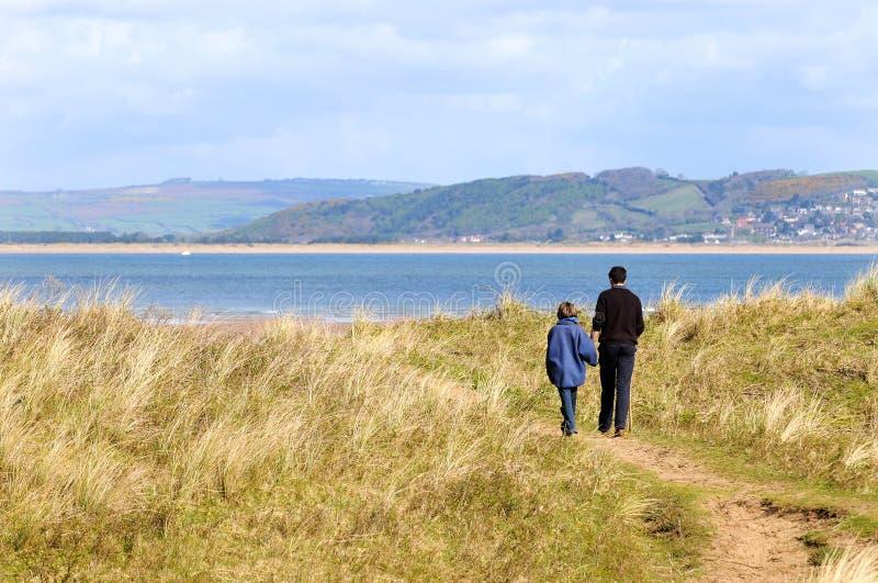 Pai e filha na caminhada ao longo da costa fotos de stock