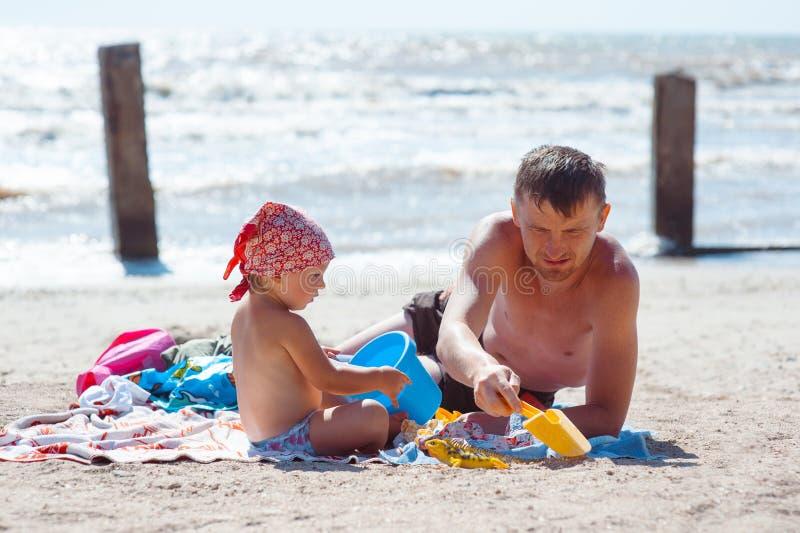 Pai e filha no castelo de jogo e de constru??o da praia da areia fotografia de stock royalty free