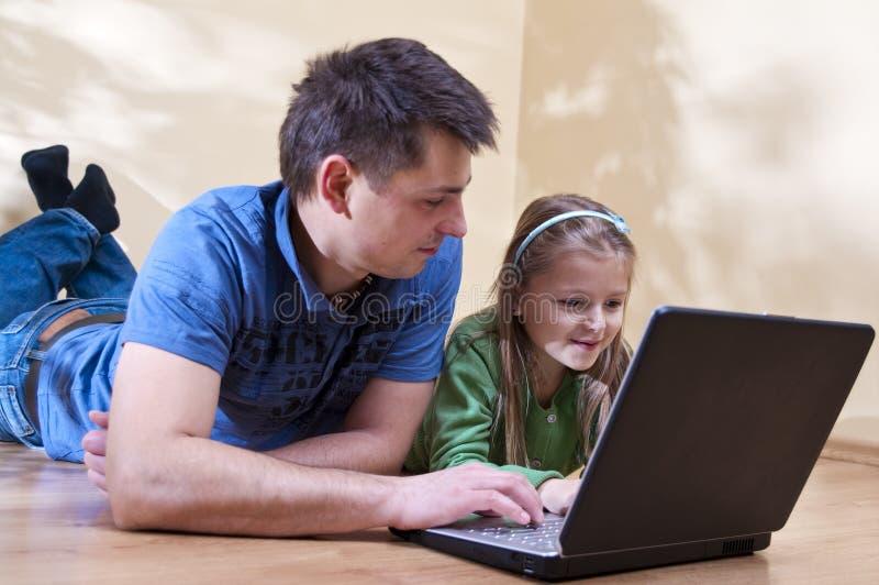 Pai e filha no portátil imagem de stock royalty free