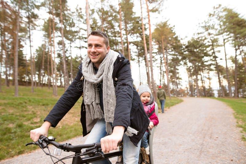 Pai e filha novos junto na bicicleta no parque do outono fotos de stock royalty free