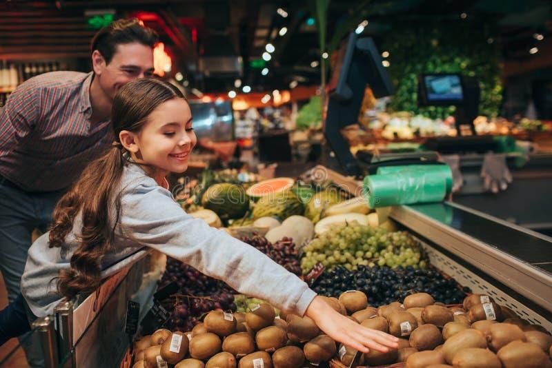 Pai e filha novos na mercearia A filha positiva feliz alcança para fora o quivi com mão Olhar positivo do pai em foto de stock