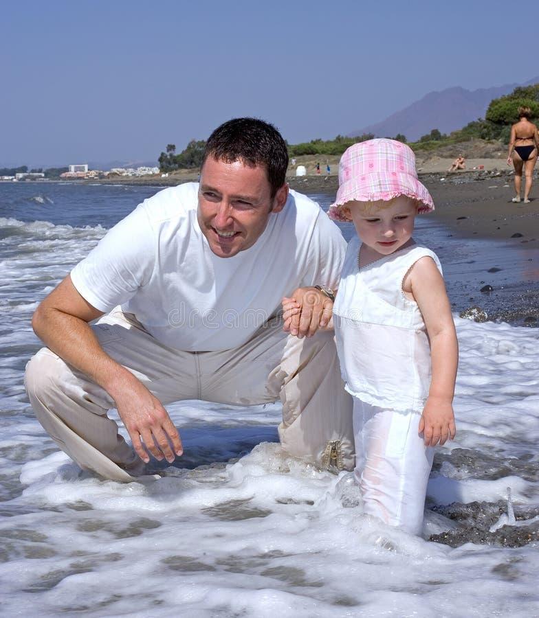 Pai e filha novos na praia em férias foto de stock