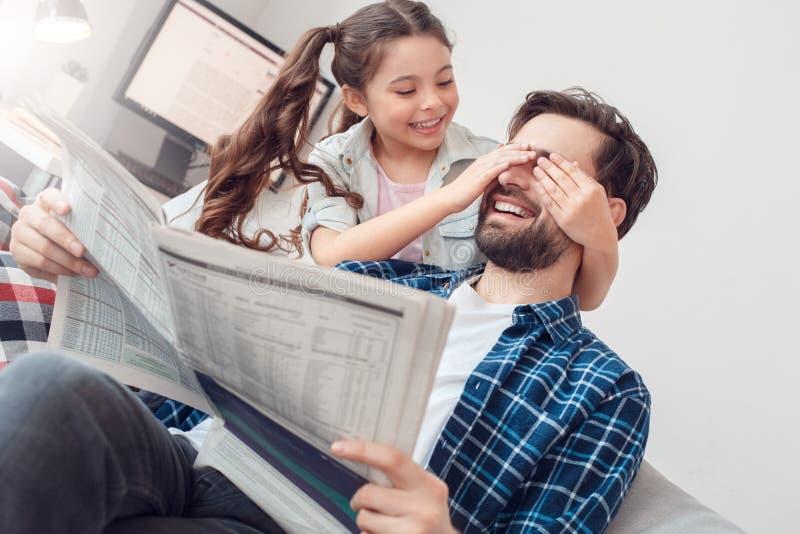 Pai e filha pequena em casa que sentam os olhos da coberta da menina do sorriso do pai foto de stock royalty free