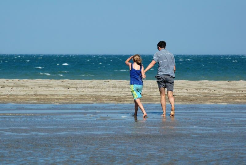 Pai e filha que andam na praia fotografia de stock royalty free