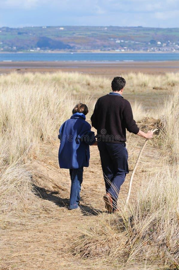 Pai e filha que andam perto da costa imagens de stock