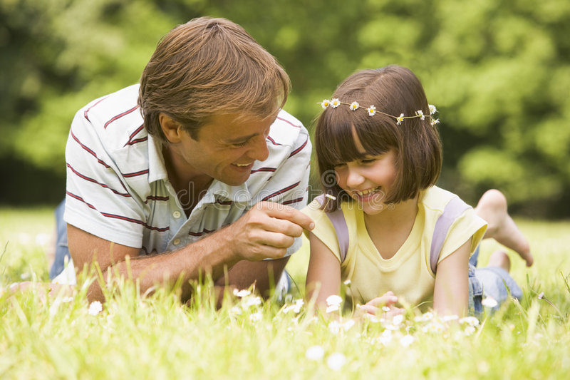 Pai e filha que encontram-se ao ar livre com flores imagens de stock royalty free