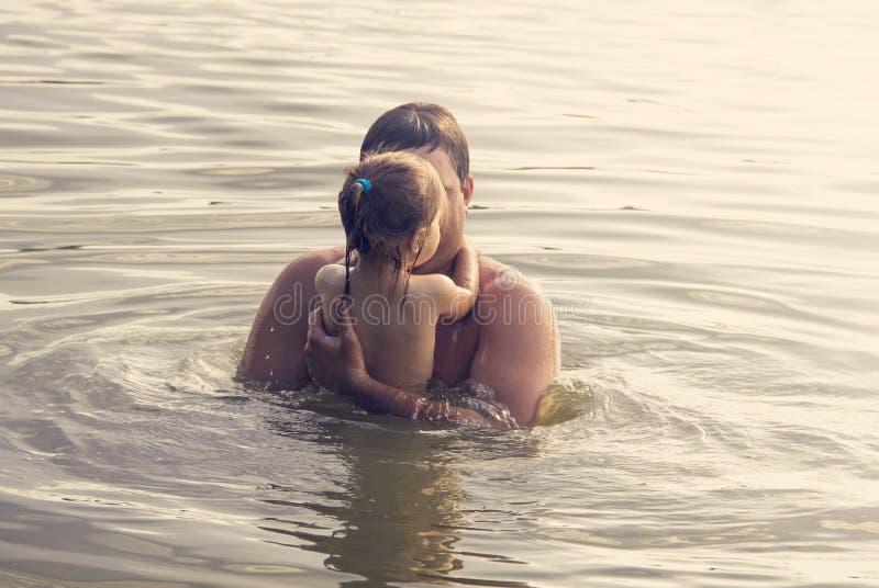 Pai e filha que jogam junto no mar no por do sol foto de stock