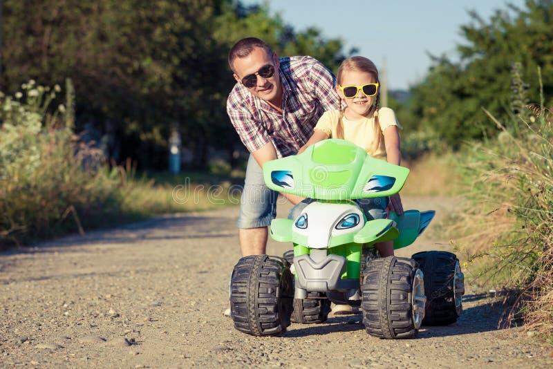 Pai e filha que jogam na estrada no tempo do dia foto de stock royalty free