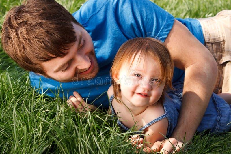 Pai e filha que jogam na grama fotografia de stock royalty free