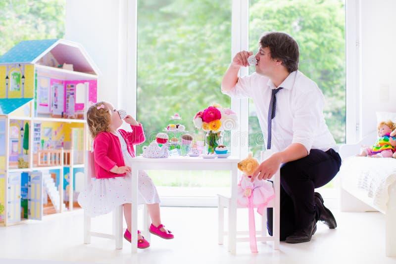 Pai e filha que jogam o tea party da boneca foto de stock