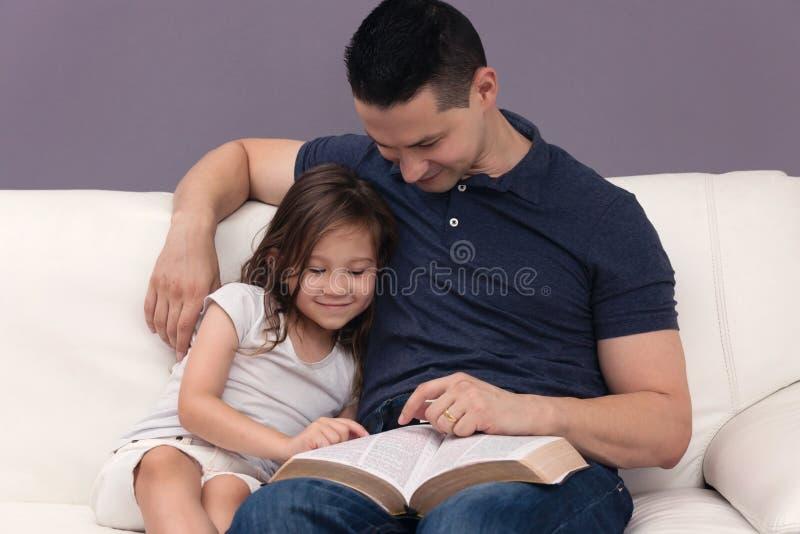 Pai e filha que leem a Bíblia foto de stock royalty free
