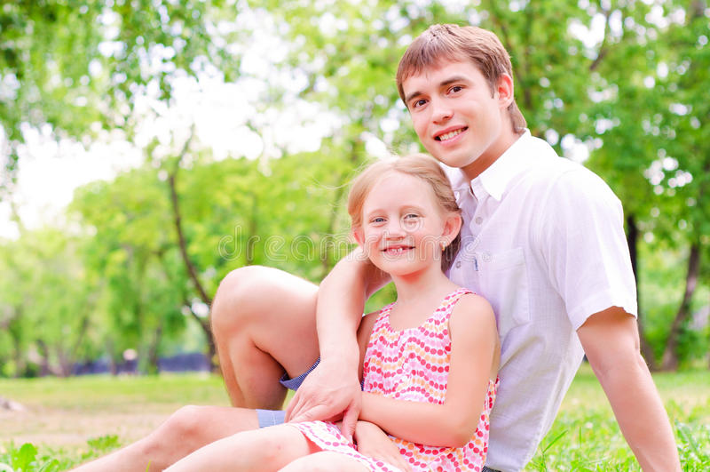Pai e filha que sentam-se junto na grama imagem de stock
