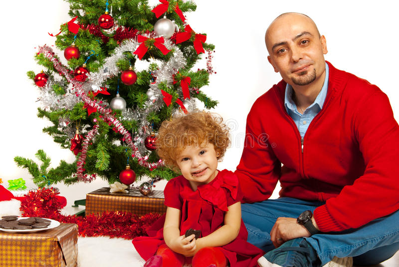 Pai e filha que sentam-se perto da árvore do Xmas fotografia de stock