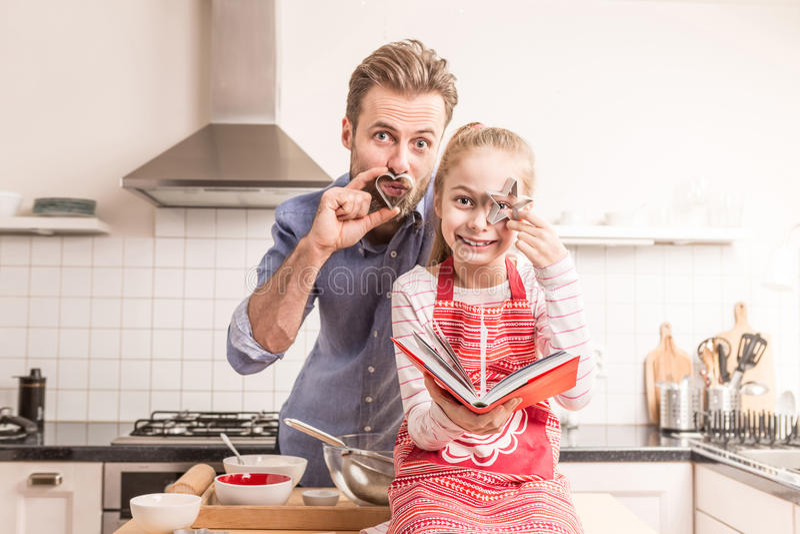 Pai e filha que têm o divertimento na cozinha - cozimento imagem de stock