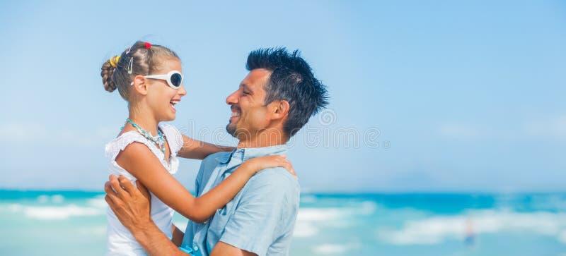 Pai e filha que têm o divertimento na praia imagens de stock royalty free