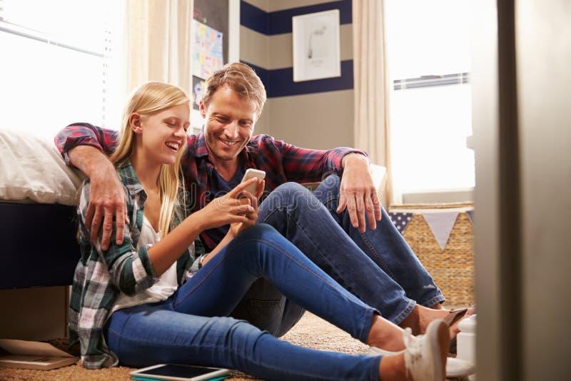 Pai e filha que usa o telefone esperto junto foto de stock