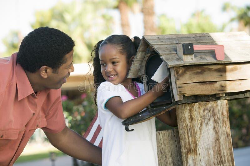 Pai e filha que verificam o correio na caixa postal doméstica imagem de stock