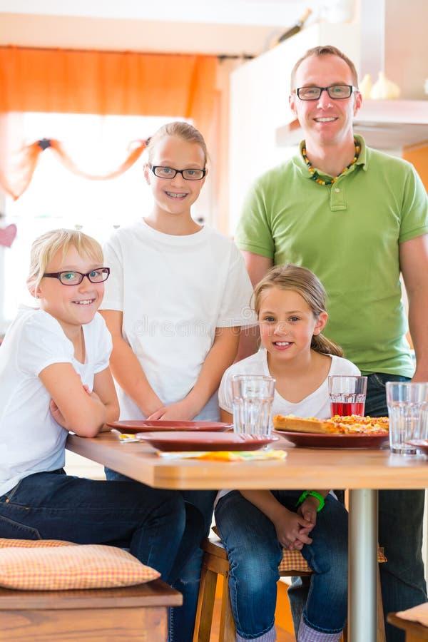 Pai e filhas em comer da cozinha saudável imagens de stock
