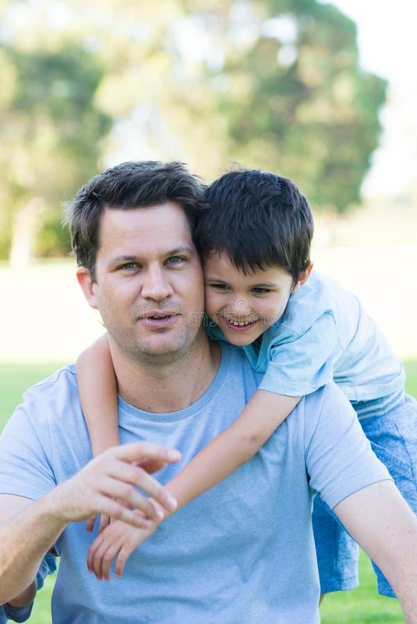 Pai e filho alegres do retrato no parque fora fotos de stock royalty free