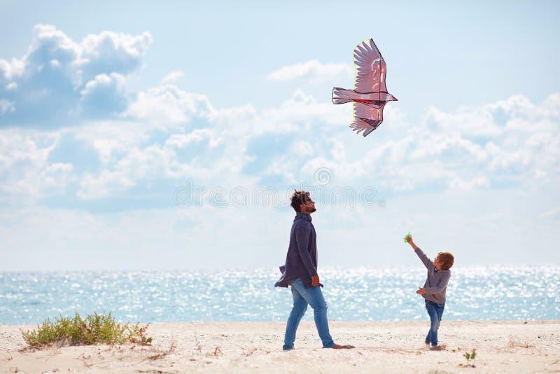Pai e filho alegres, família que lança o papagaio no Sandy Beach, no dia ventoso fotografia de stock