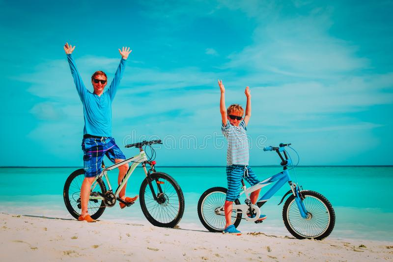 Pai e filho e biking felizes na praia imagens de stock royalty free