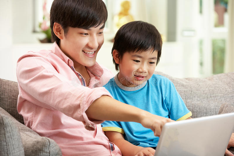Pai e filho chineses que usa o portátil foto de stock