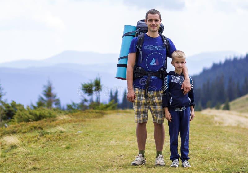 Pai e filho com as trouxas que caminham junto em montanhas cênicos do verde do verão Paizinho e criança que estão de apreciação a imagens de stock