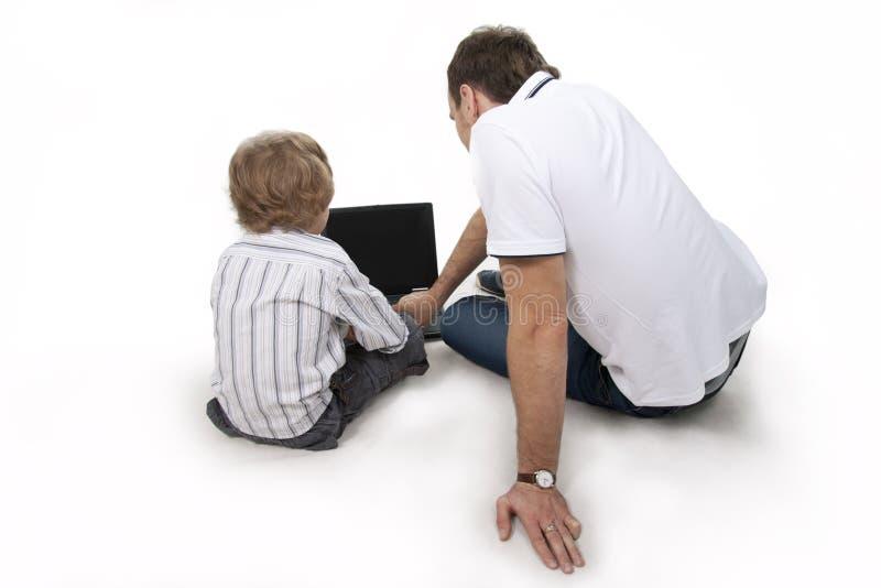 Pai e filho com o computador. fotografia de stock