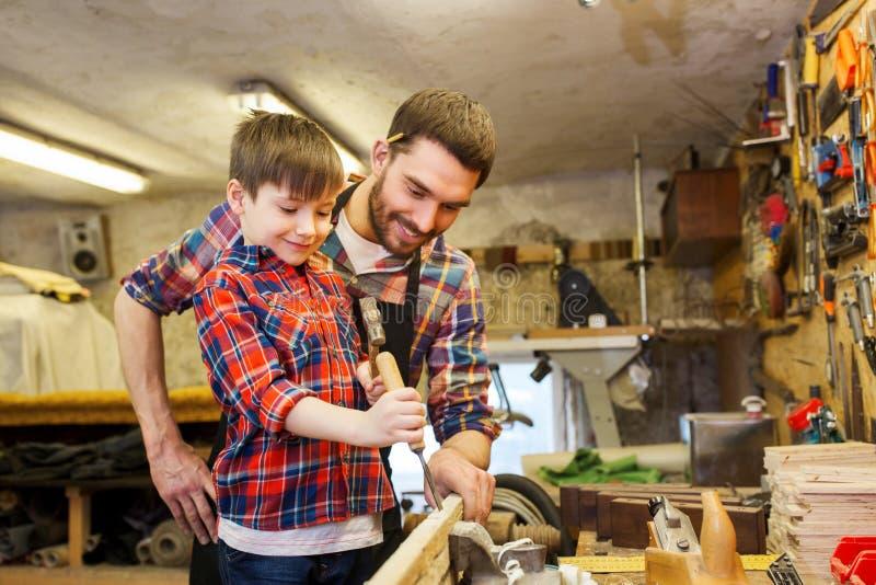 Pai e filho com o formão que trabalha na oficina imagens de stock royalty free