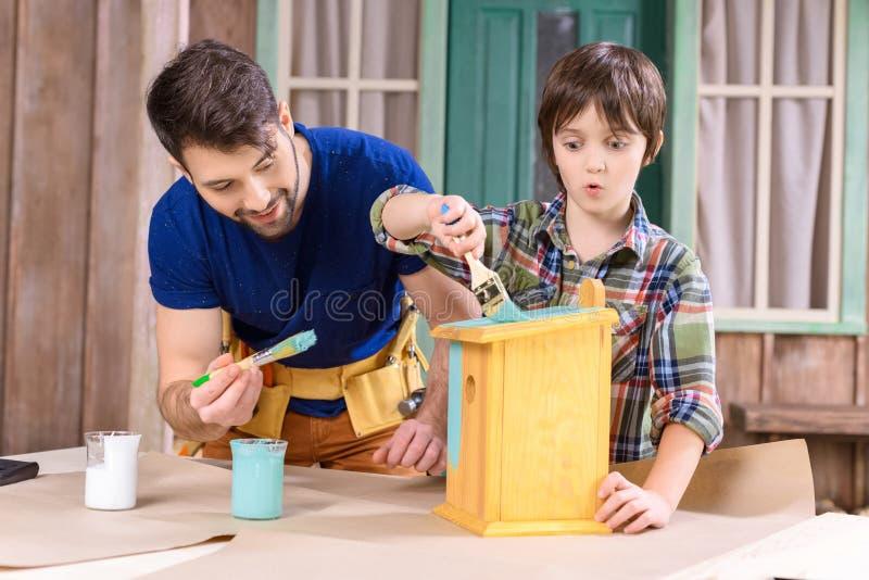 Pai e filho com os pincéis que pintam o aviário de madeira junto imagem de stock royalty free