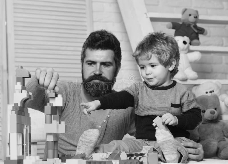 Pai e filho com rostos felizes criam construções coloridas com tijolos de brinquedo Homem e garoto jogam juntos na parede de made fotografia de stock
