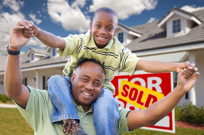 Pai e filho com sinal e HOME dos bens imobiliários foto de stock