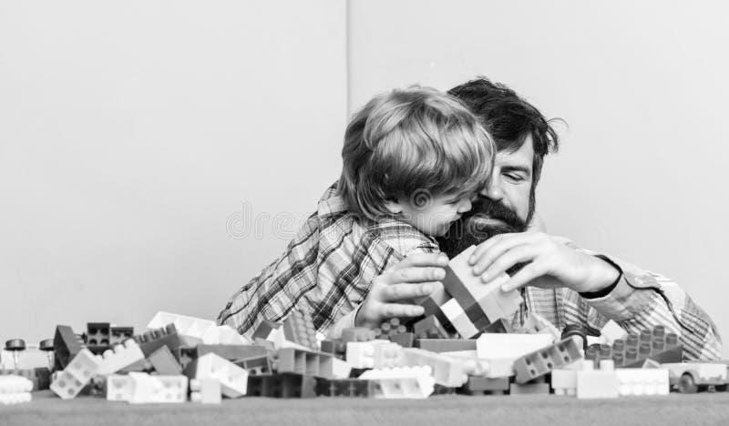 Pai e filho criam construções Homem barbudo e filho brincam juntos Atirem formas de se relacionar com o seu filho Filho do pai imagem de stock royalty free