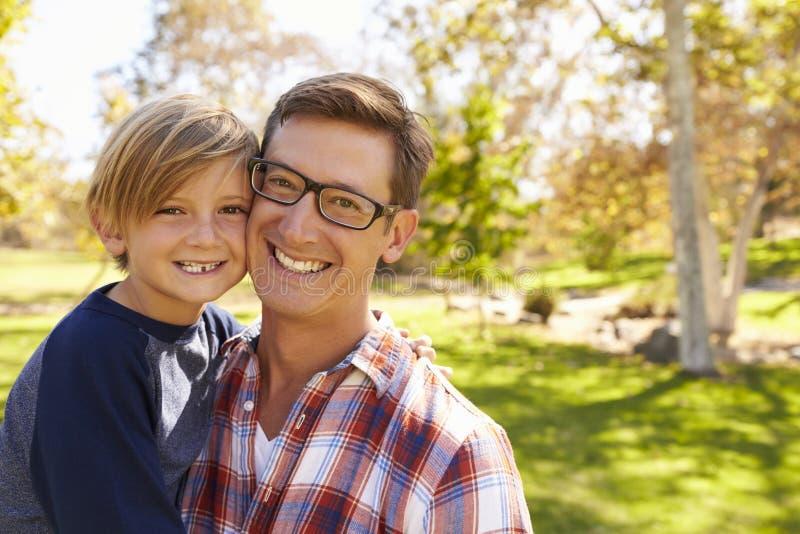 Pai e filho da criança de sete anos que sorri à câmera em um parque imagem de stock royalty free