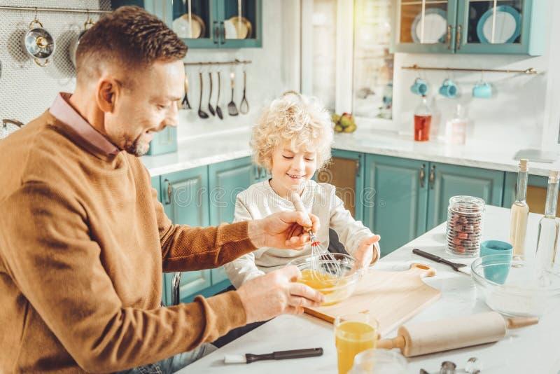 Pai e filho de irradiação que cozinham a torta para sua mãe bonita imagens de stock