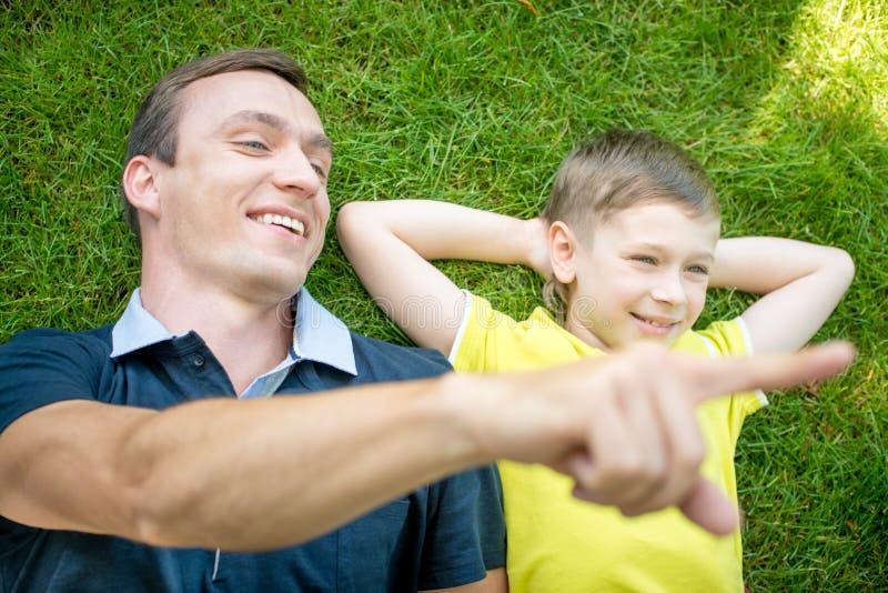 Pai e filho de sorriso que encontram-se em apontar da grama imagem de stock royalty free