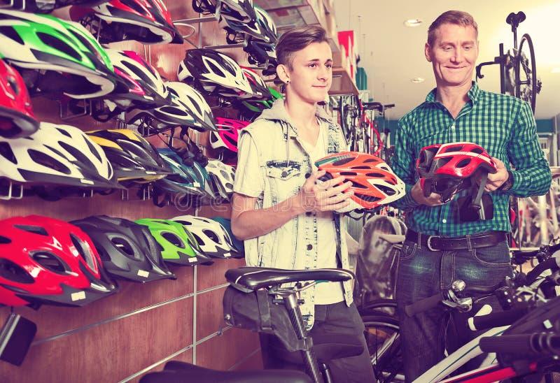Pai e filho de sorriso que escolhem o capacete bicycling foto de stock royalty free