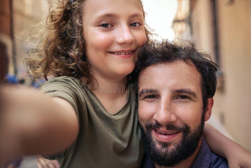 Pai e filho de sorriso que tomam selfies em uma rua da cidade fotos de stock