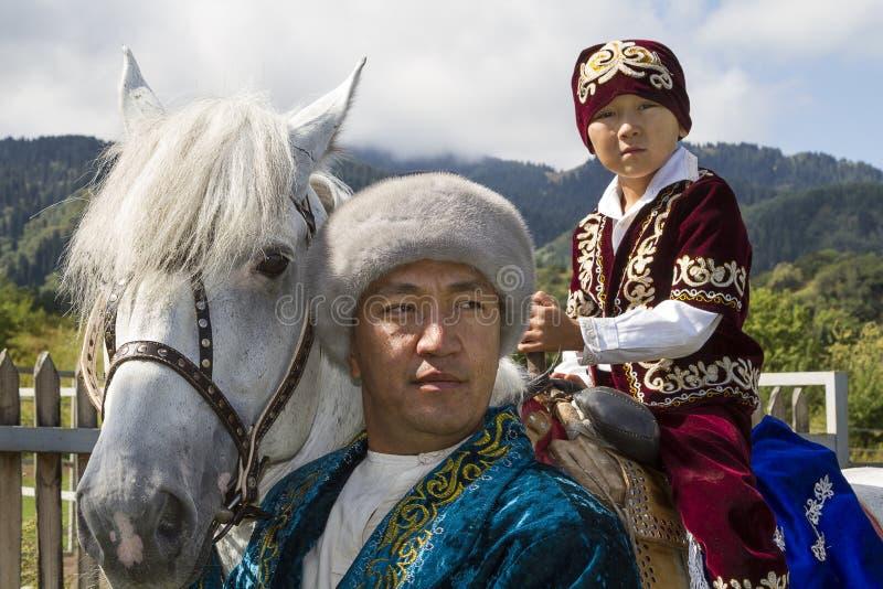 Pai e filho do Cazaque em seu cavalo em vestidos tradicionais na mostra do kazakh de jogos nacionais imagens de stock royalty free