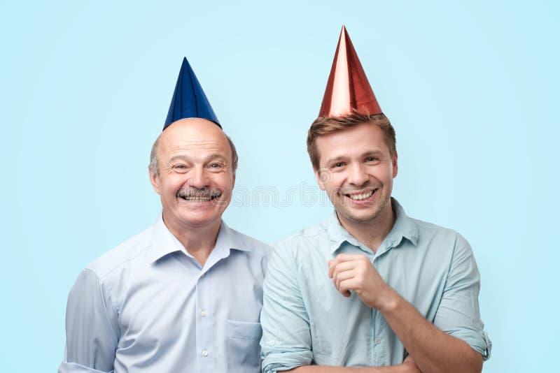 Pai e filho do feliz aniversario que têm o olhar alegre, sorrindo alegremente imagens de stock royalty free