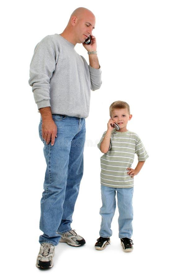 Pai e filho em telemóveis imagens de stock royalty free