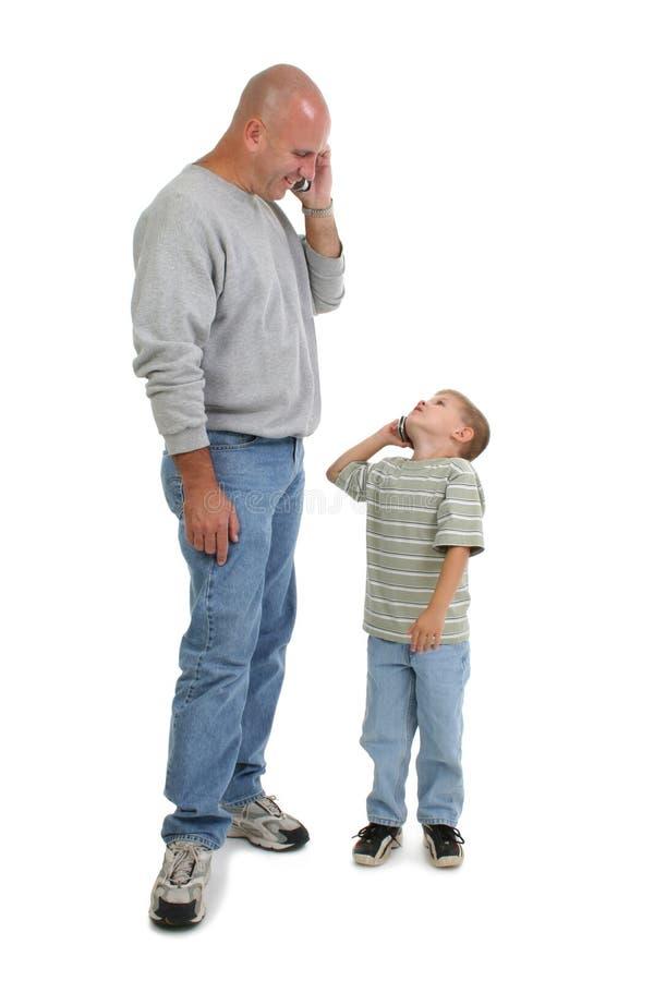 Pai e filho em telemóveis fotografia de stock