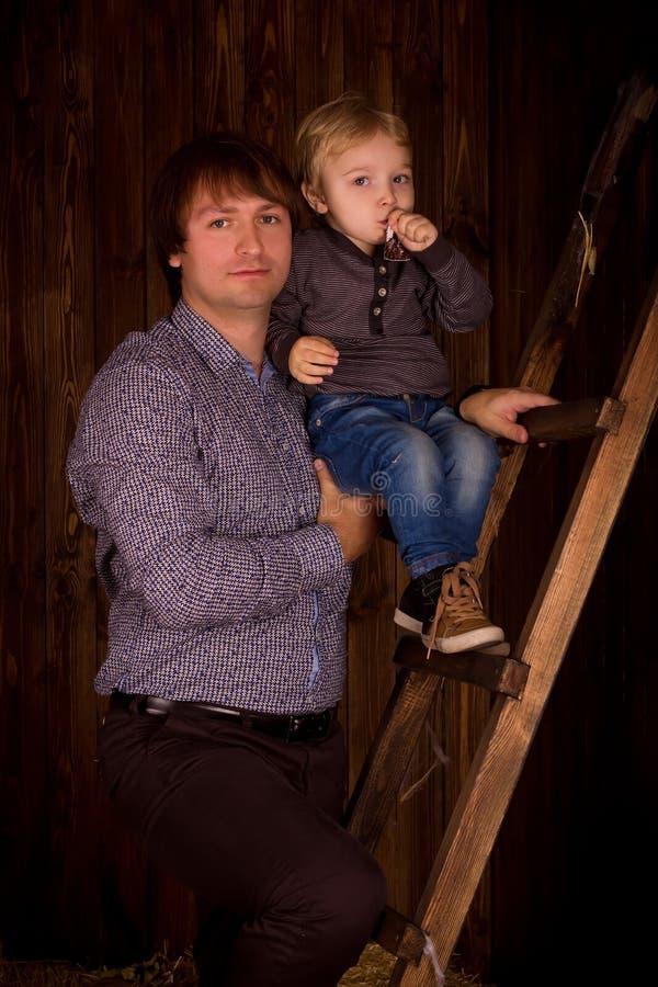 Pai e filho em um interior de madeira fotografia de stock royalty free
