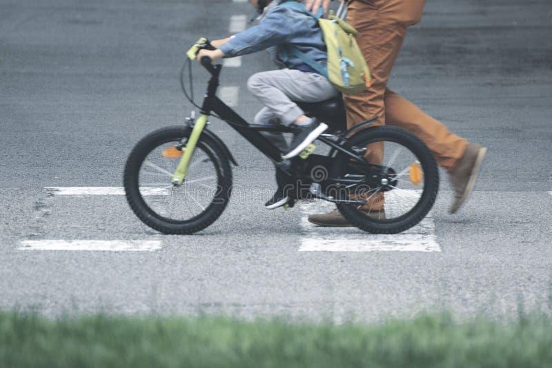 Pai e filho em uma bicicleta que cruza a passagem à escola Conceito do progenitor e espaço vazio da cópia foto de stock royalty free