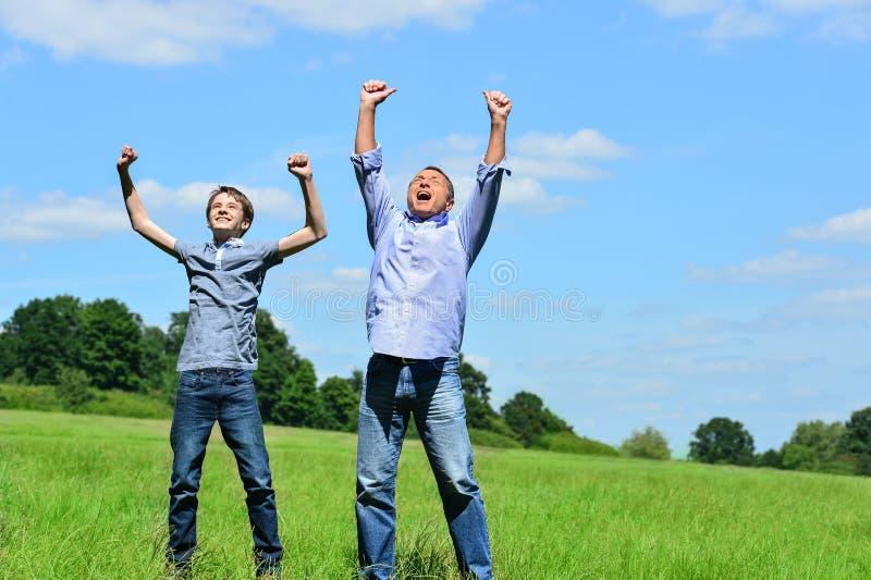 Pai e filho entusiásticos fora imagem de stock